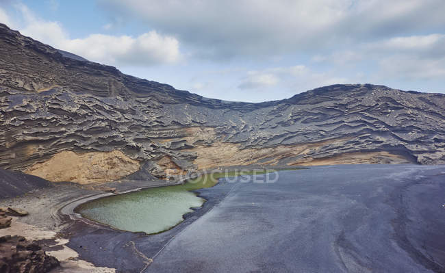 Volcanic landscape with lake, Lanzarote, Canary Islands, Spain — Stock Photo