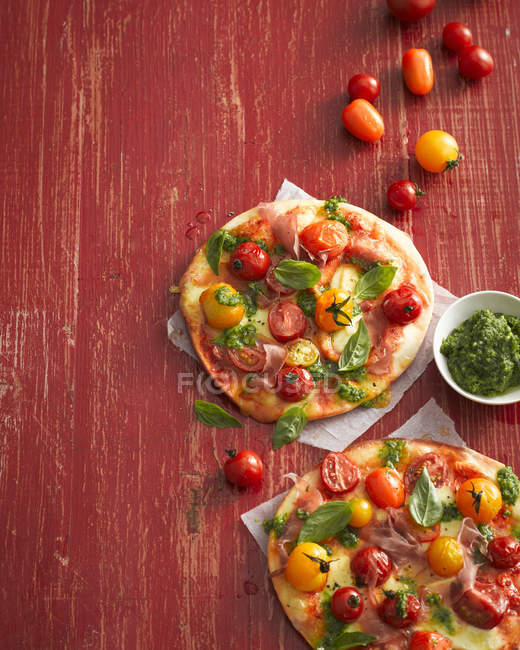 Top view of tomato, basil and prosciutto pizzas — Stock Photo