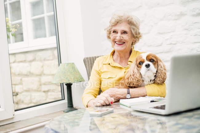 Старший жінка з собакою дивиться геть при використанні ноутбука — стокове фото