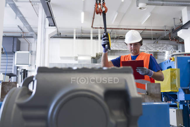 Mid adult man wearing hard hat operating machine, looking down at clipboard — Stock Photo
