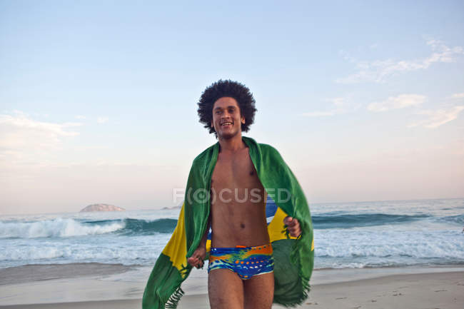 Young man on beach, wrapped in Brazilian Flag — Stock Photo