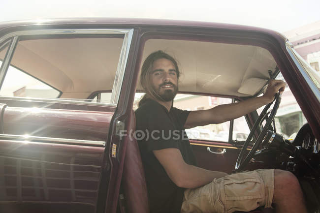 Retrato de hombre joven en viaje por carretera en la conducción de automóvil vintage, ciudad del cabo, Sudáfrica - foto de stock