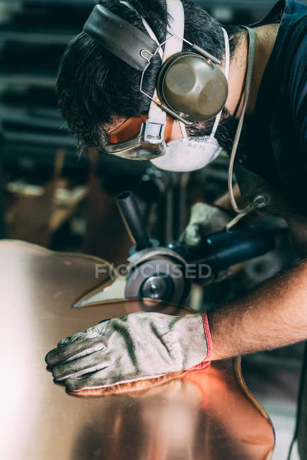 Metalworker grinding the edge of copper in forge workshop — Stock Photo