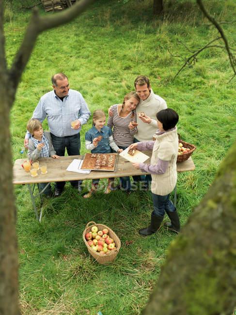 Persone che mangiano torta di mele con cesto — Foto stock
