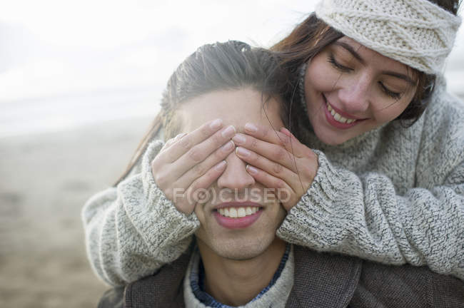 Young woman covering mans eyes — Stock Photo