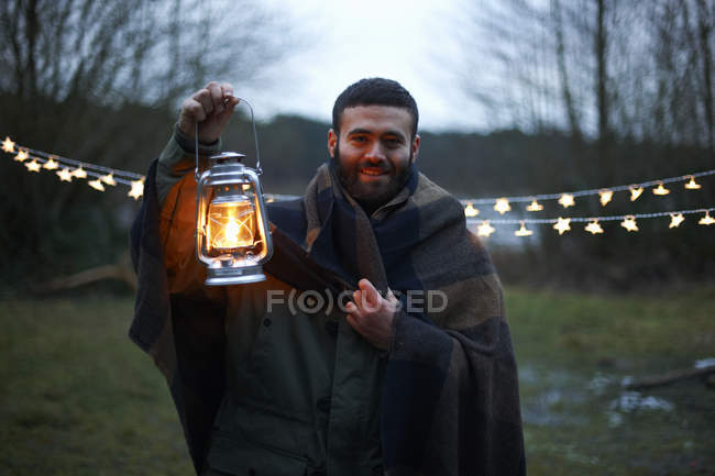 Young male camper holding up lantern whilst wrapped in blanket in woods — Stock Photo