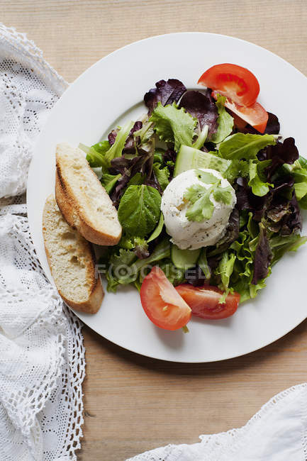 Top view of mixed salad with sliced baguette — Stock Photo