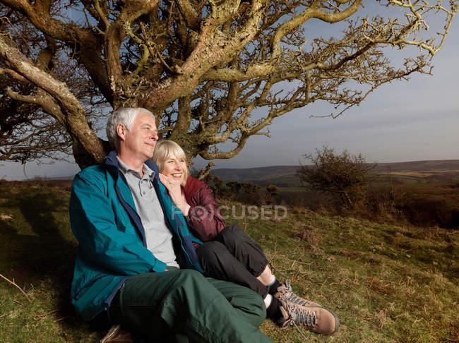 Coppia matura seduta contro albero — Foto stock