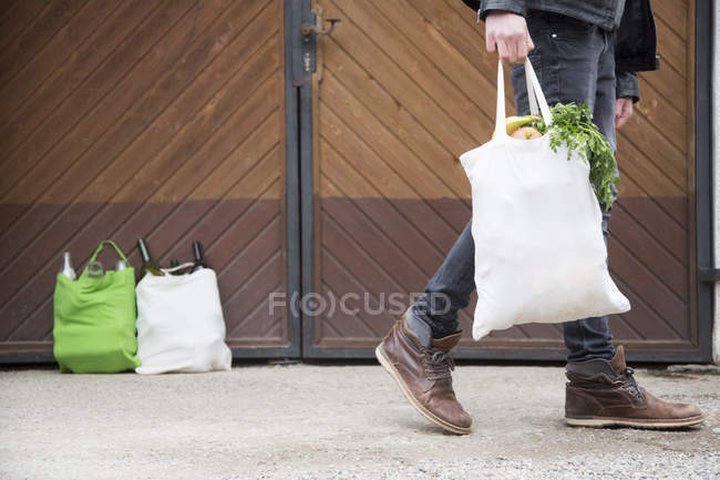 Teenage boy carrying reusable shopping bag full of fruit and veg, with bottles for recycling in yard — Stock Photo