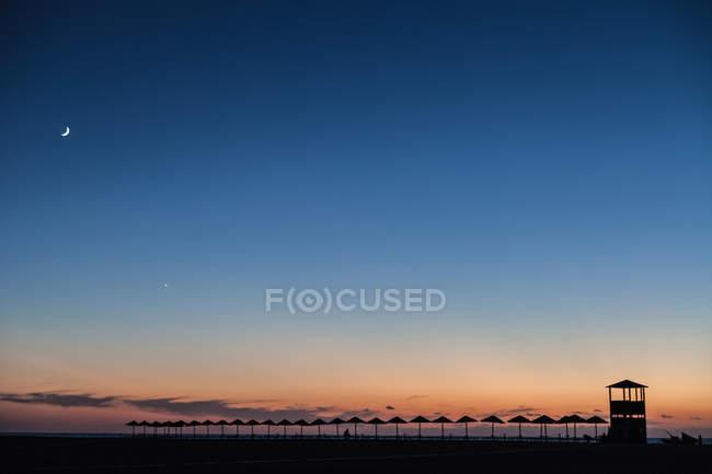 Silhouette di ombrelloni al tramonto, Piscinas, Sardegna, Italia — Foto stock