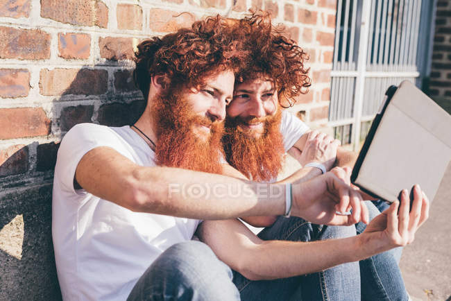 Young male hipster twins with red hair and beards browsing digital tablet on sidewalk — Stock Photo