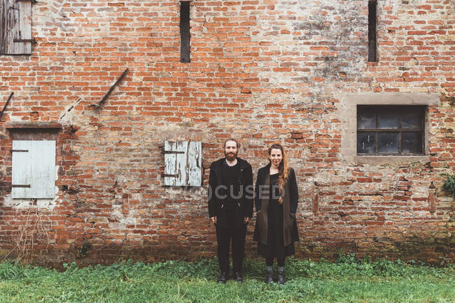 Ritratto di coppia davanti al vecchio edificio agricolo in mattoni — Foto stock