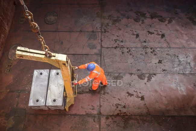 Visão de alto ângulo do trabalhador que descarrega lingotes de liga metálica do porão do navio — Fotografia de Stock