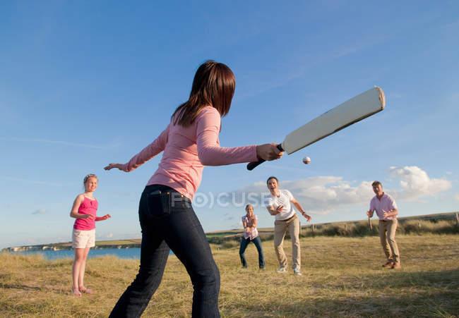 Сім'я граючи крикет разом на відкритому повітрі — стокове фото
