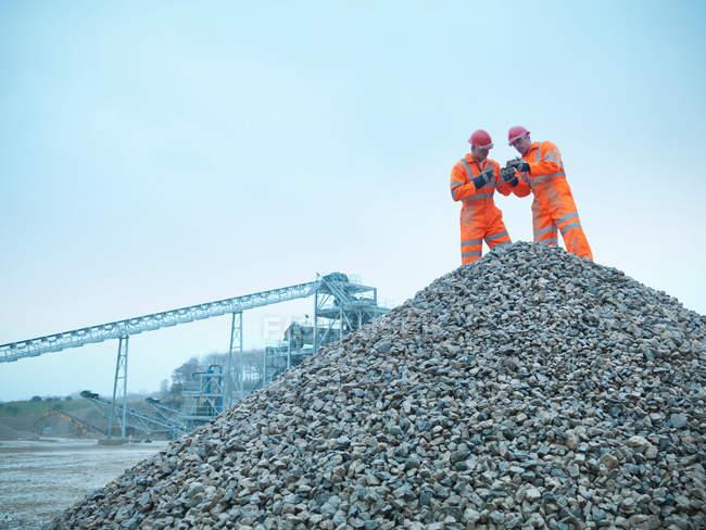 Deux mineurs inspectant des stocks de pierres extraites de carrières — Photo de stock