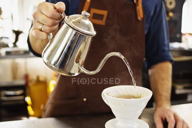 Close up de barista derramando água fervente em filtro de café — Fotografia de Stock