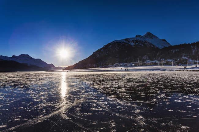Paisagem com lago congelado e montanhas na luz solar — Fotografia de Stock