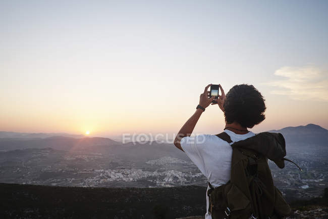 Rear view of young man photographing landscape and sunset on smartphone, Javea, Spain — Stock Photo