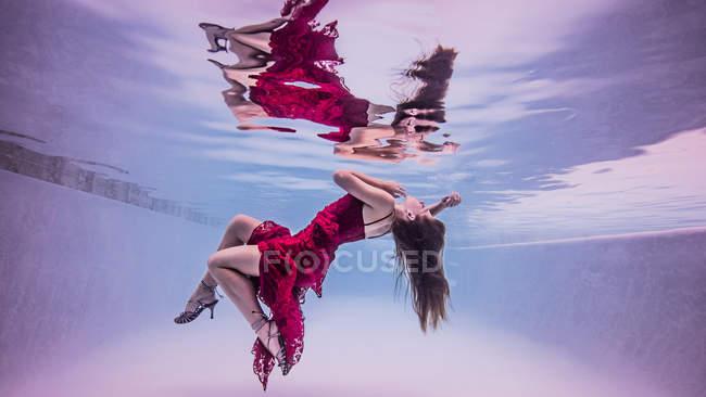 Vue sous-marine de la fille portant une robe rouge et des chaussures à talons hauts, flottant vers la surface de l'eau — Photo de stock