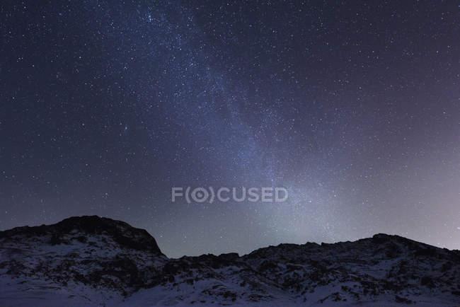 Montagna accidentata su un paesaggio innevato sotto il cielo stellato notturno, Kleifarvatn, Islanda — Foto stock