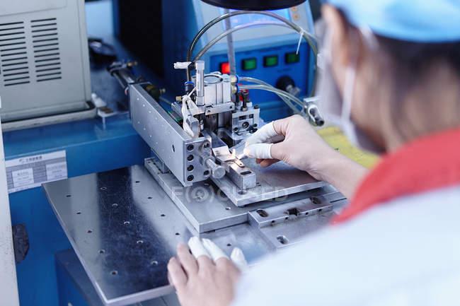 Trabajador en fábrica de baterías de cigarrillos electrónicos - foto de stock