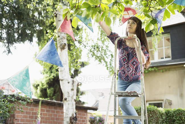 Женщина висит овсянка в саду по дому — стоковое фото