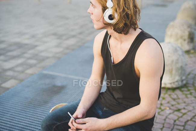 Young man sitting at sidewalk listening to headphone music — Stock Photo