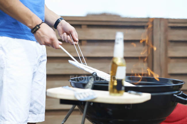 Cropped shot of mid adult man barbecuing at rooftop barbecue — Stock Photo