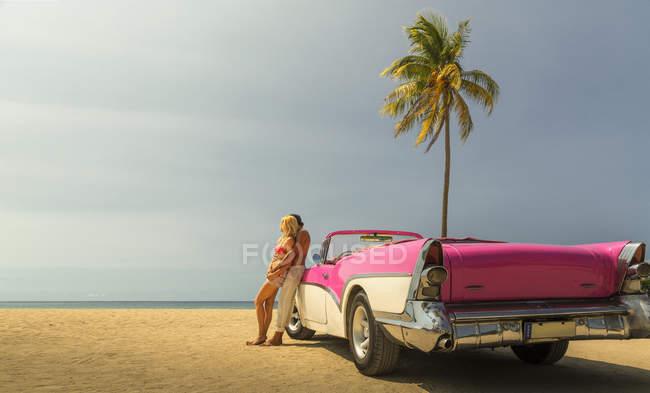 Coppie al lato Convertible sulla spiaggia — Foto stock