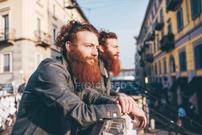 Молодые близнецы-хипстеры с рыжими волосами и бородами, выглядывающие с городского моста — стоковое фото