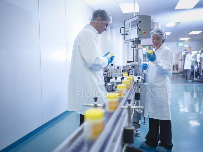 Workers inspecting packaging in pharmaceutical factory — Photo de stock