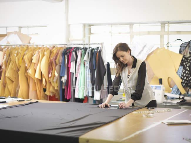 Модный дизайнер измеряет ткань в студии дизайна моды — стоковое фото