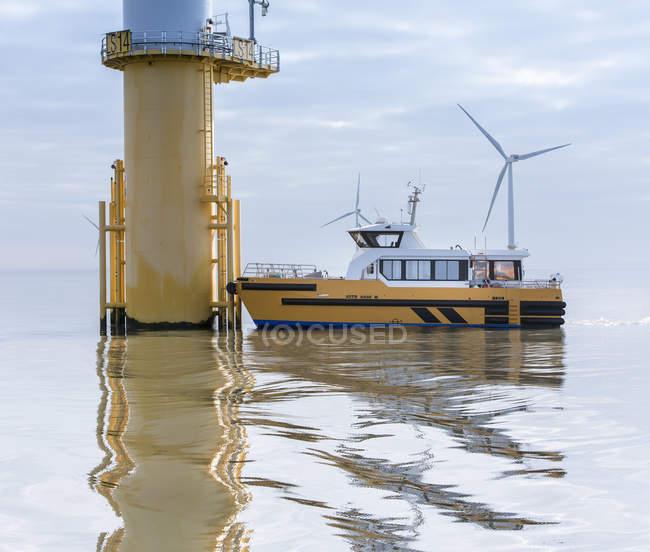 Imbarcazione di servizio e turbina eolica presso il parco eolico offshore — Foto stock
