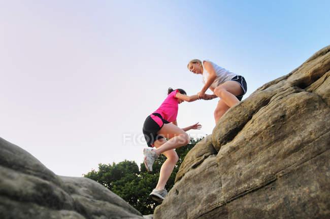 Zwei junge Läuferinnen helfen sich gegenseitig auf der Felsformation — Stockfoto