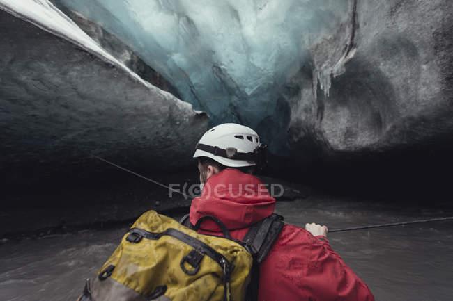 Человек пересекает реку с веревкой в ледяной пещере, ледник Ватнайокалл, Национальный парк Ватнайокалл, Исландия — стоковое фото