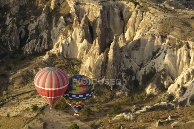 Pair of hot air balloons floating next to each other in valley, Cappadocia, Anatolia, Turkey — Stock Photo