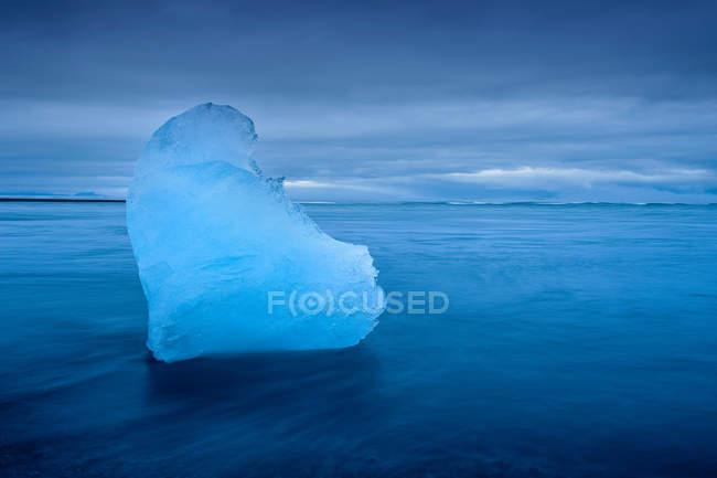 Iceberg galleggiante in acque glaciali con cielo nuvoloso — Foto stock