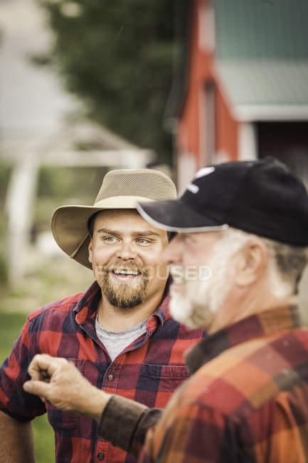 Bauern in karierten Hemden plaudern auf Ackerland — Stockfoto