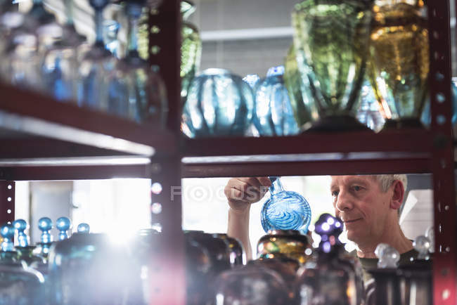 Glassblower inspecting finished glassware — Stock Photo