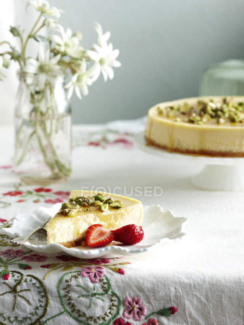 Slice of ricotta honey cheesecake and strawberries on plate — Stock Photo