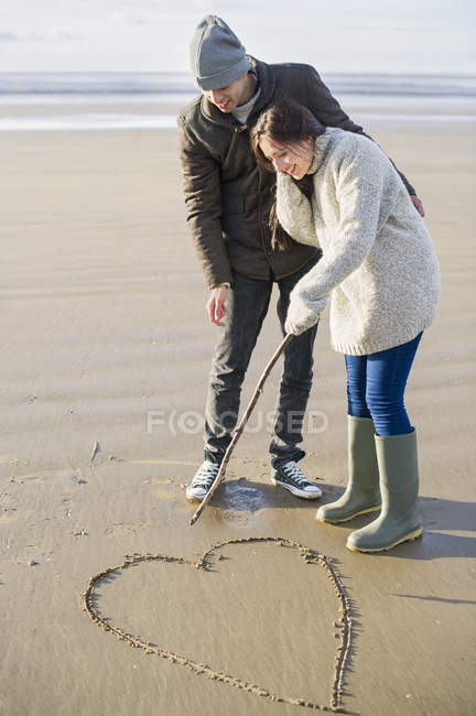 Young couple drawing heart in sand, Brean Sands, Somerset, England — Stock Photo