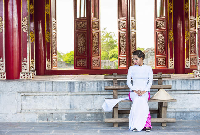 Mid adult woman in imperial palace wearing ao dai dress sitting on bench looking down, Hue, Vietnam — Stock Photo