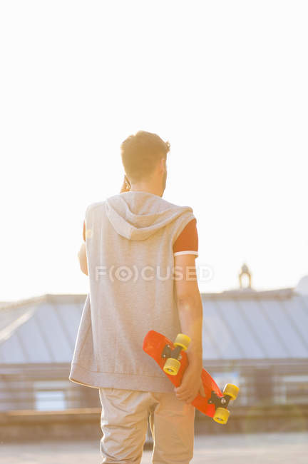 Mid adult man on rooftop, holding skateboard, rear view — Stock Photo