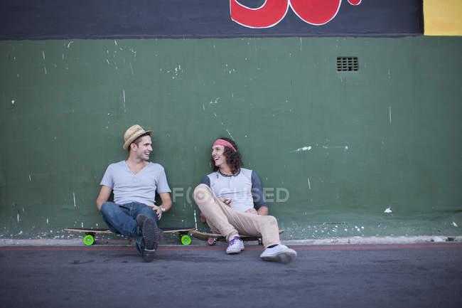 Deux amis masculins adultes s'asseyant sur des planches à roulettes et bavardant — Photo de stock