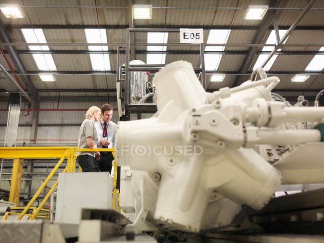 Trabalhadores da fábrica olhando para a máquina — Fotografia de Stock
