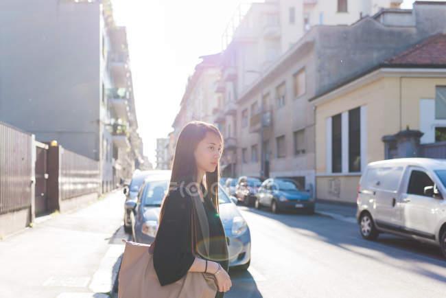 Jovem mulher passeando pela rua da cidade iluminada pelo sol — Fotografia de Stock