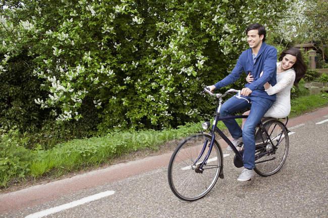 Молода пара посміхається під час їзди на велосипеді — стокове фото