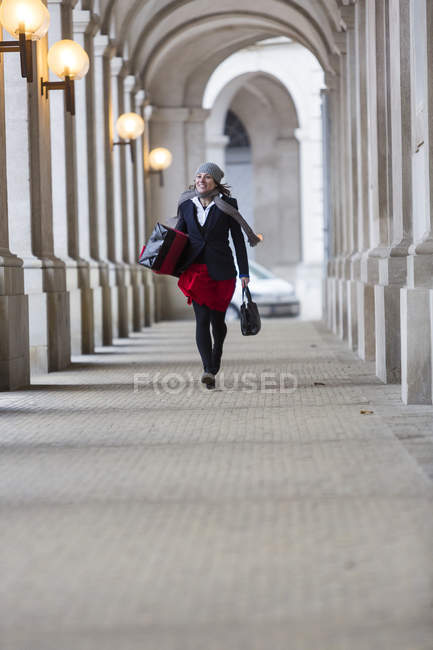 Mature woman with Christmas gift walking through city  colonnade — Stock Photo