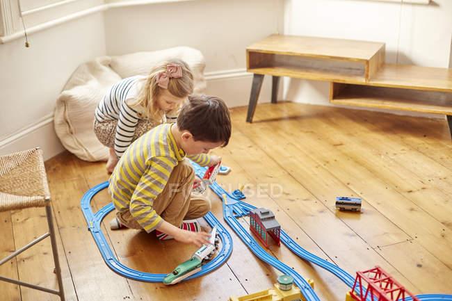 Молода дівчина і хлопчик грає з іграшкового поїзда набір — стокове фото