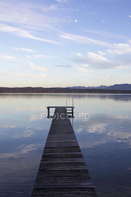 Jetée en bois et ciel nuageux réfléchissant dans l'eau du lac — Photo de stock